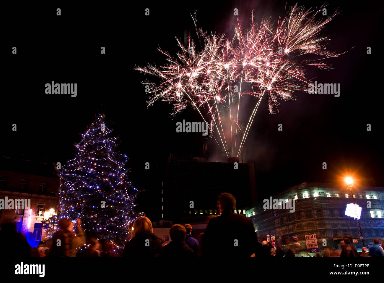 Crowds of people watching the fireworks exploding into the night sky during the Christmas Tree Lights switch on - Stock Image