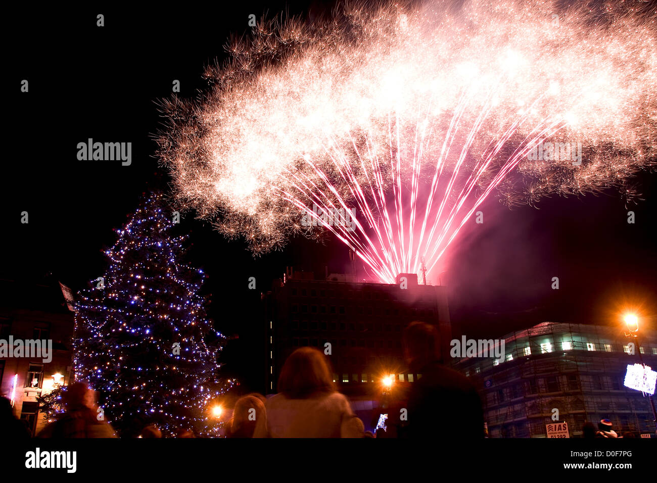 People looking at the Fireworks exploding and filling up the night sky during the Christmas Tree Lights switch on - Stock Image
