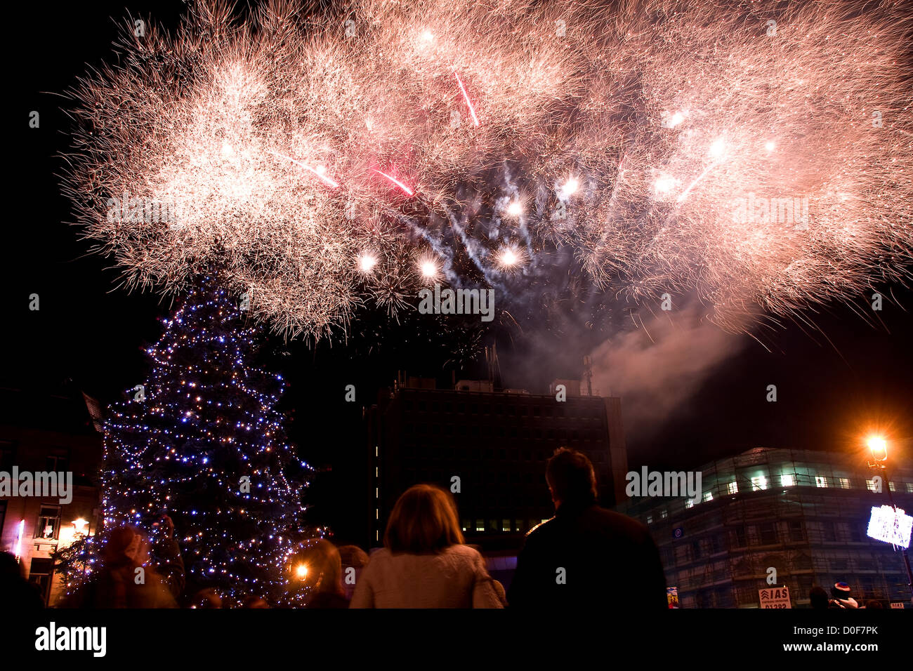 People looking up at the fireworks exploding and filling the night sky during the Christmas Tree Lights switch on - Stock Image