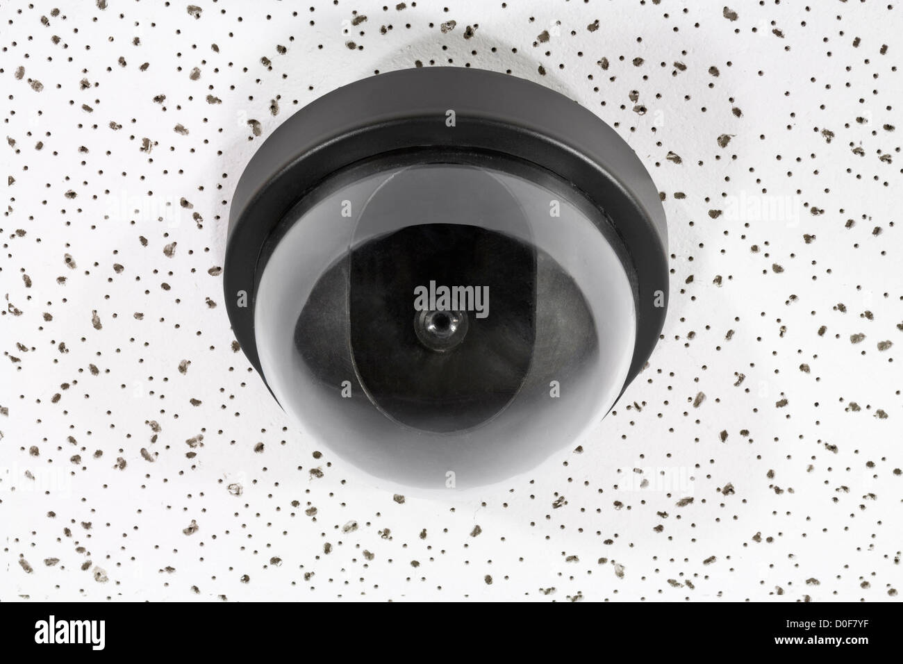 Overhead security camera globe on acoustic tile. - Stock Image