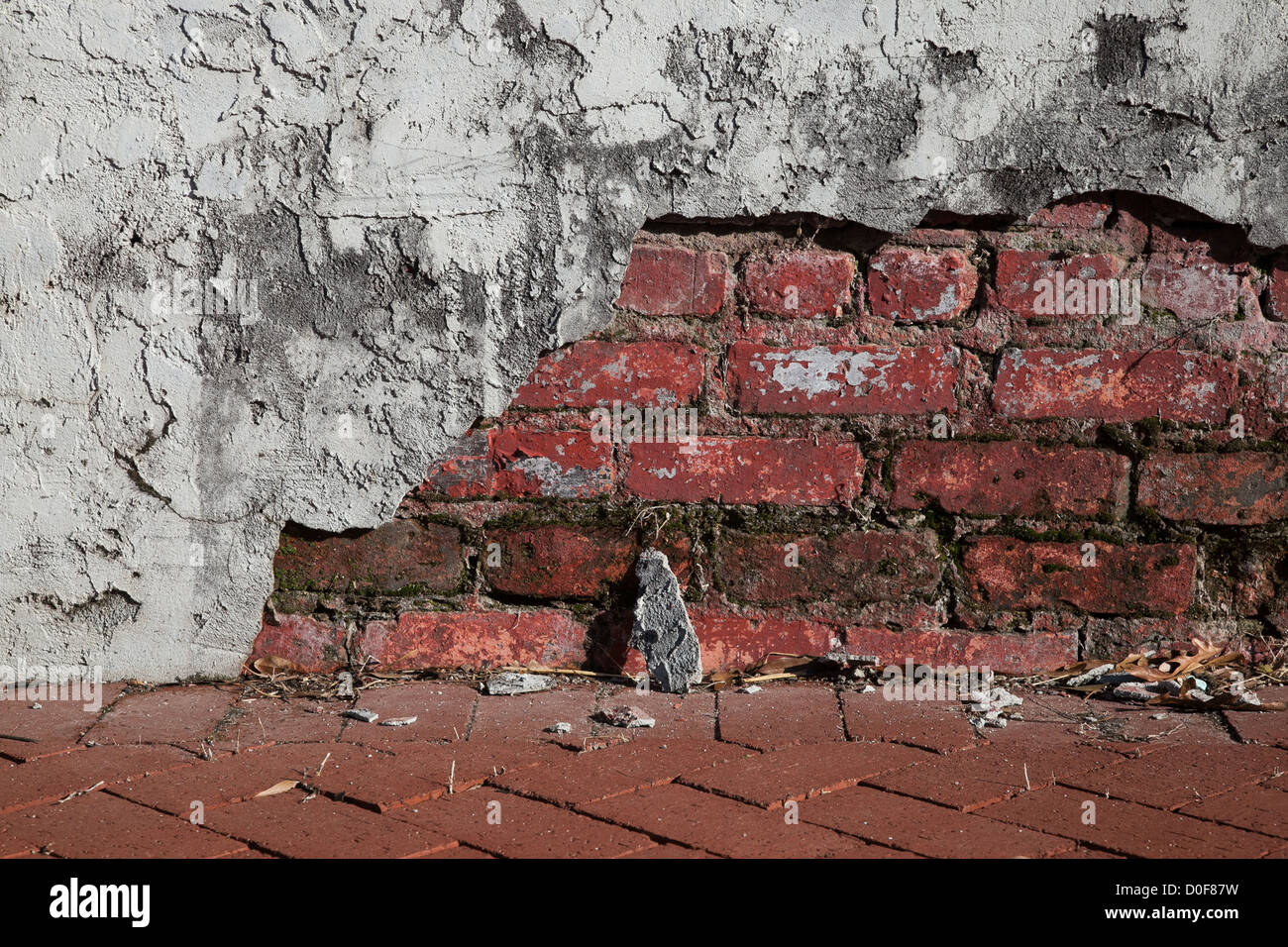 old stucco wall over red brick in a state of disrepair Stock