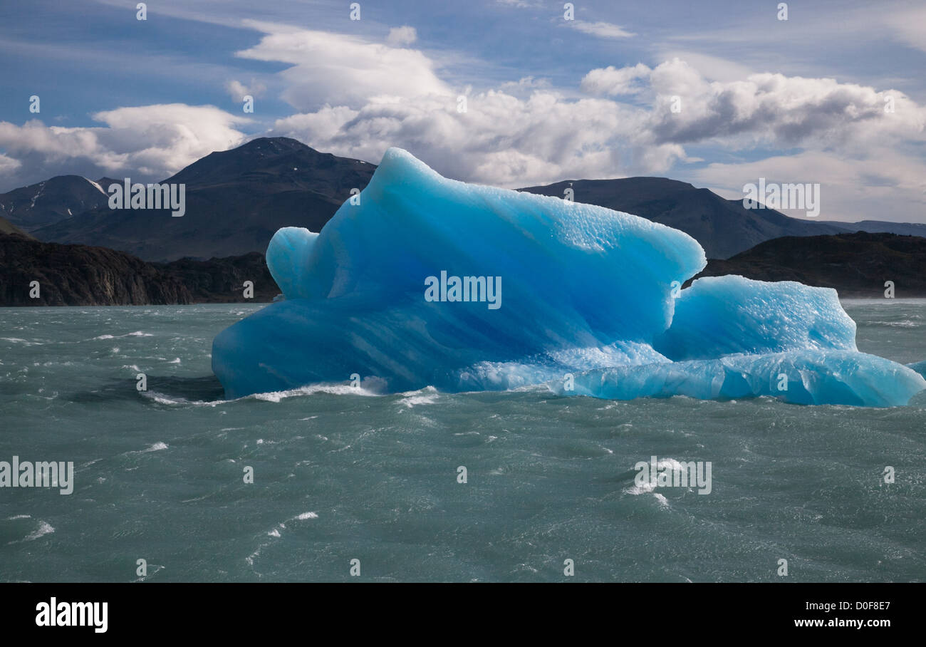 A blue iceberg floats away from the Perito Moreno Glacier in the Patagonia in Argentina - Stock Image