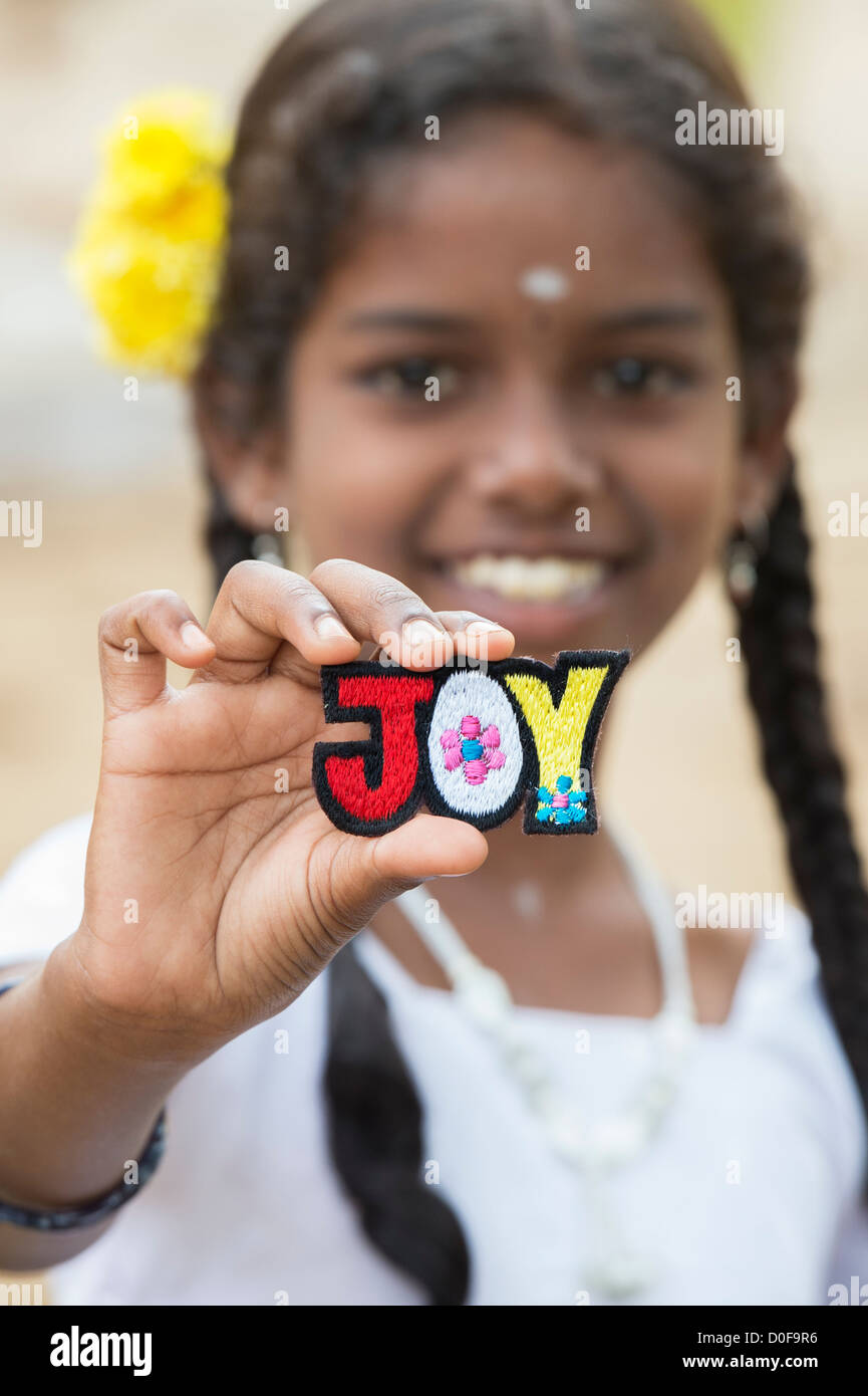 Smiling Indian girl holding a JOY multicoloured embroidery patch. India - Stock Image