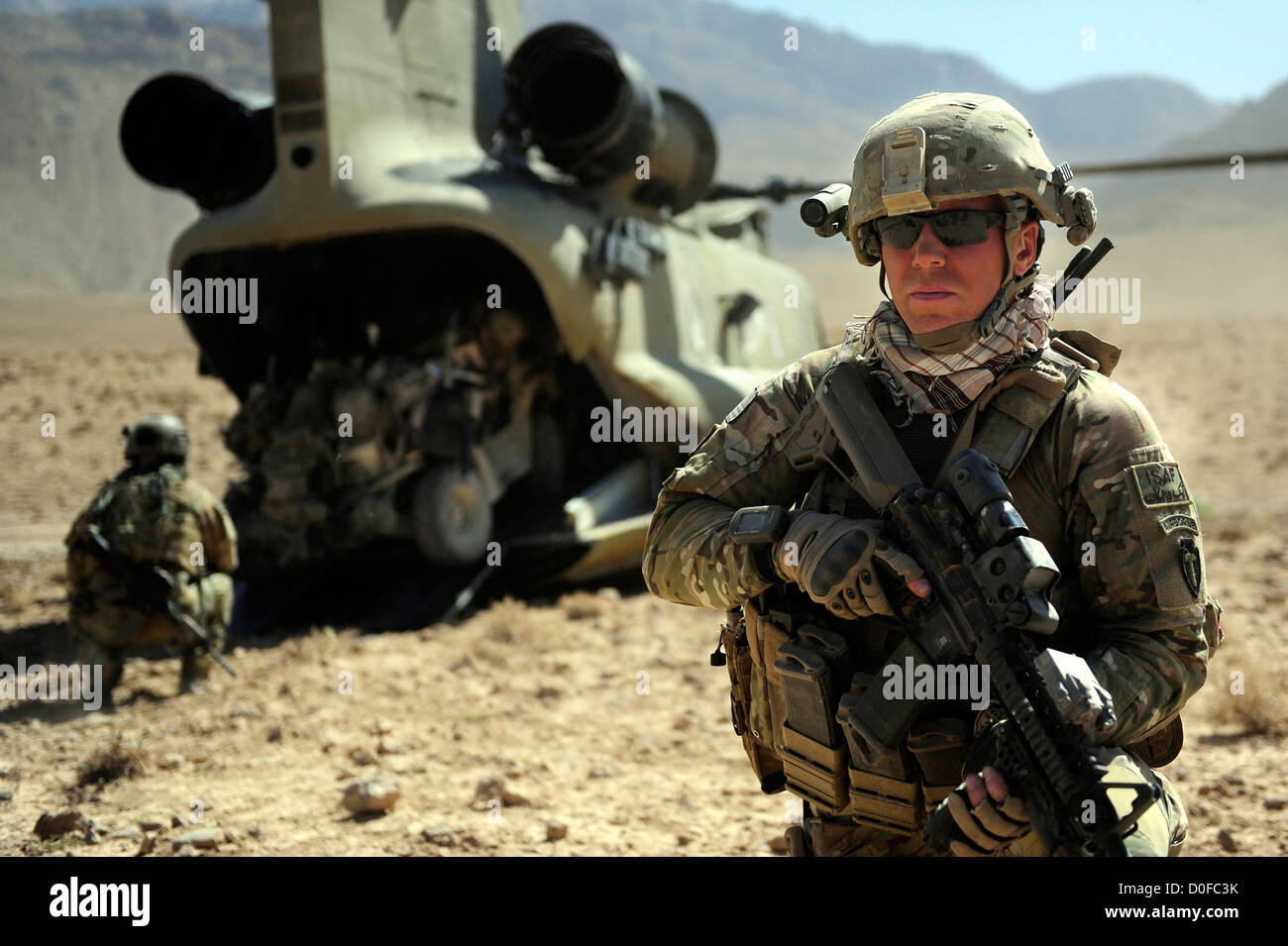 A US Army soldier secures the landing zone as his team loads a tactical vehicle into the cargo bay of a CH-47 Chinook - Stock Image