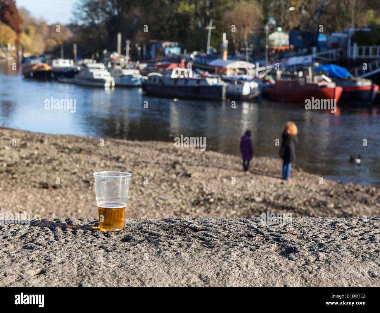A half empty beer glass is discarded  and people walk on the exposed river bed of the Thames River at Low tide Stock Photo