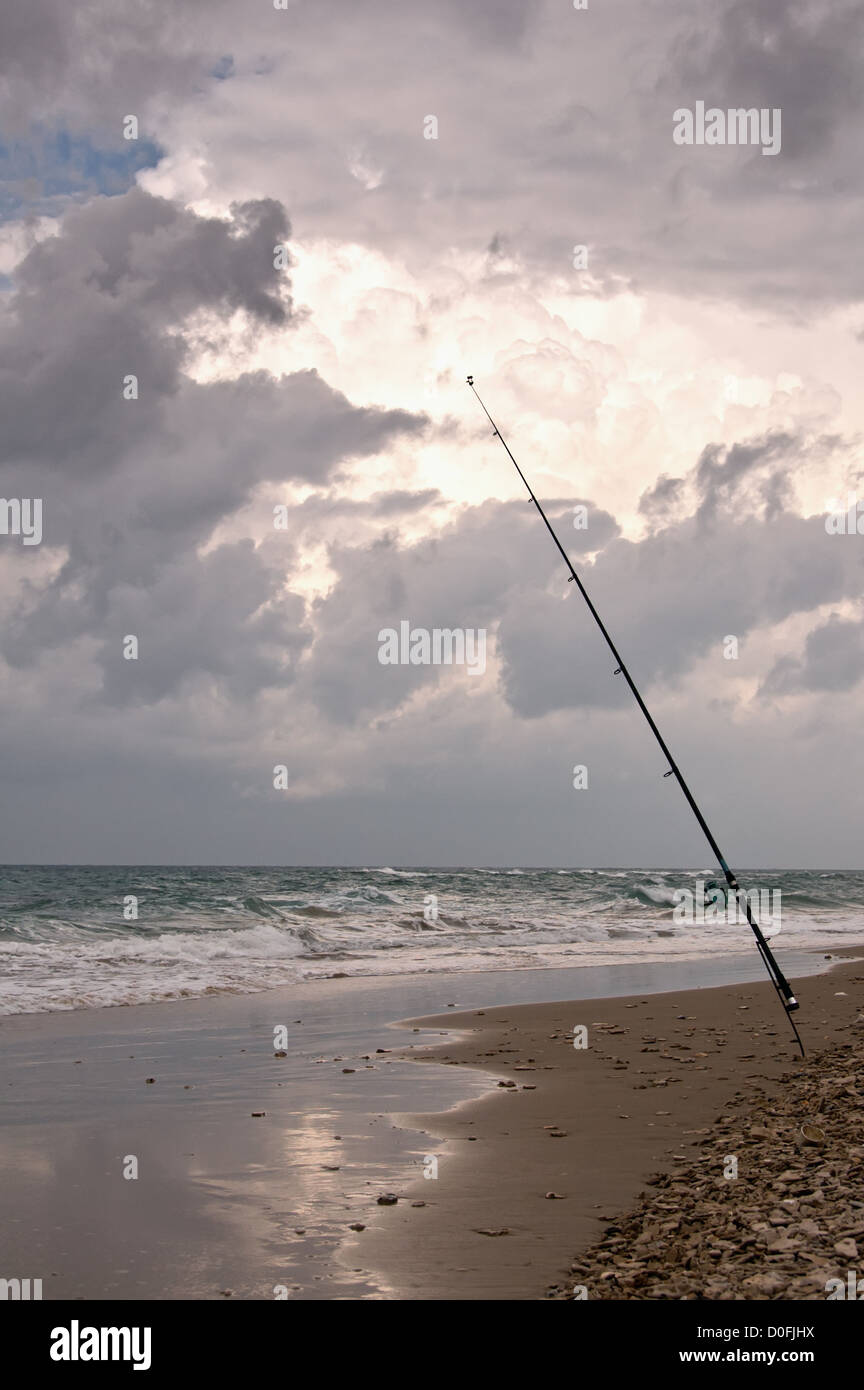 one fishing pole on an empty beach during a rainy day - Stock Image