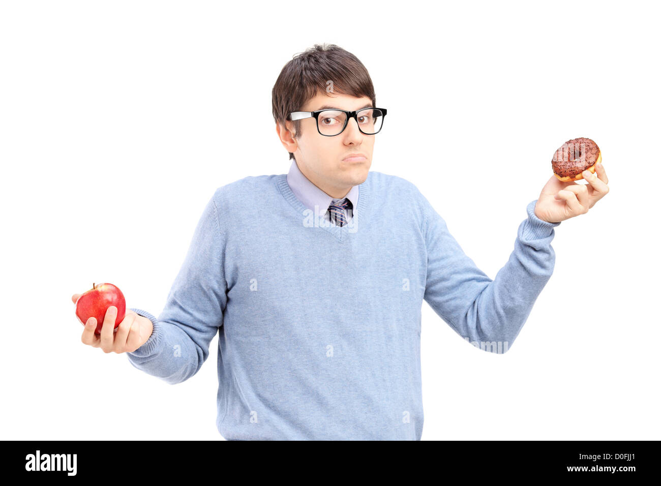 A doubtful guy holding an apple and donut trying to decide which one to eat - Stock Image