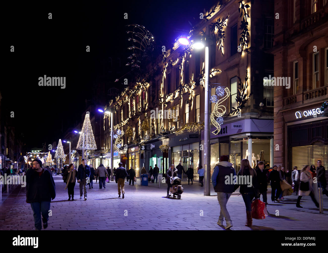 Buchanan Street Glasgow at night - November. Workers and shoppers under blue lights. Princes Square. Christmas lights. - Stock Image