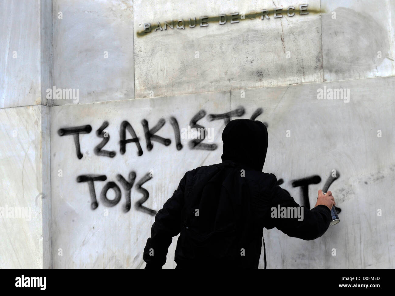 """A masked protester sprayed the words """"crushed the fascists"""" on the wall of the Banque de Grece during an anti-fascist Stock Photo"""