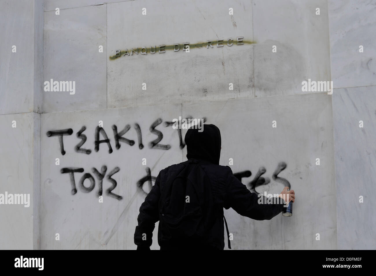 "A masked protester sprayed the words ""crushed the fascists"" on the wall of the Banque de Grece during an anti-fascist Stock Photo"