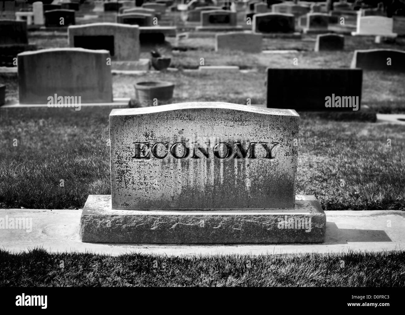 Graveyard and headstone or grave stone with economy carved as the name - Stock Image
