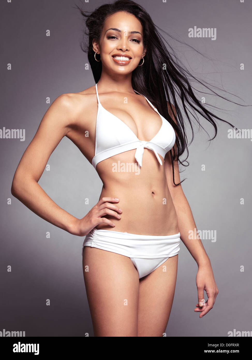 6519a0dfada Smiling young black woman wearing white bikini swimsuit isolated on gray  background