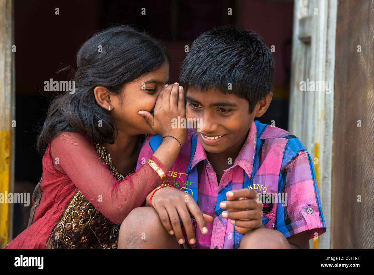 Young Indian girl whispering to a boy outside their rural Indian viilage home. Andhra Pradesh, India Stock Photo
