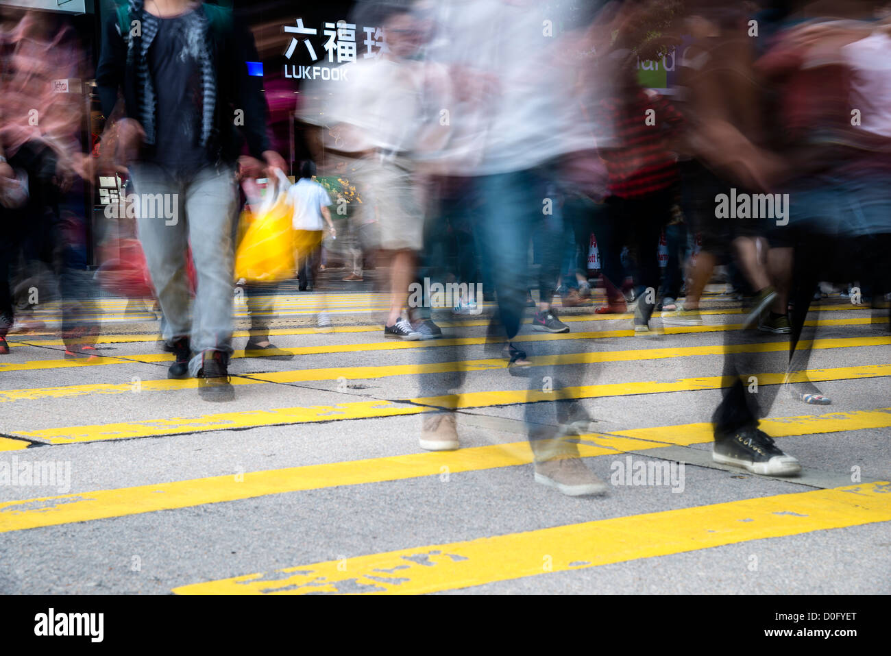 Pedestrians in blurred motion while crossing Nathan Road, Kowloon, Hong Kong, China - Stock Image