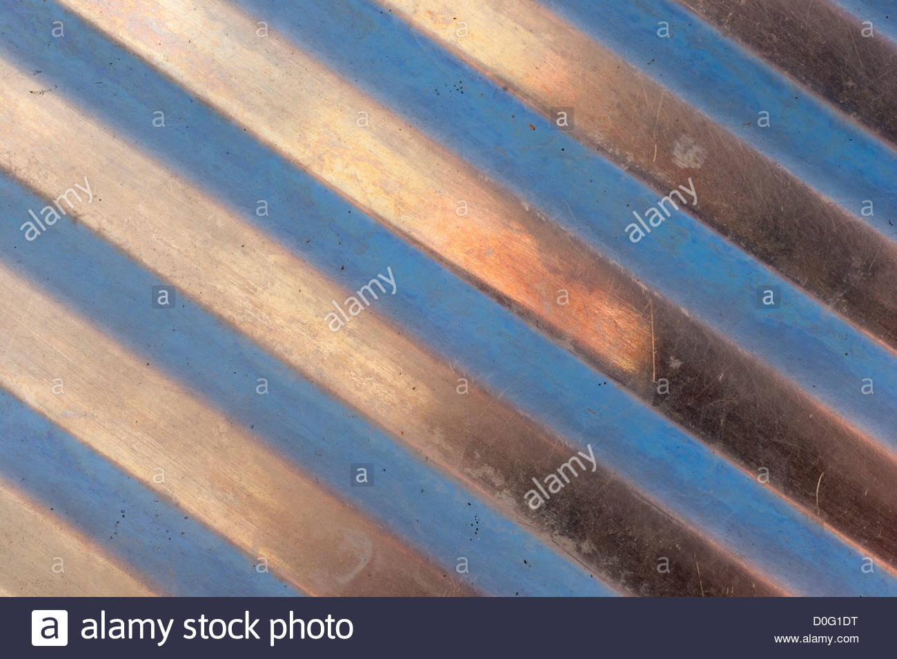 An old stainless steel draining board outside, being coloured by the reflection of washing on a washing line and - Stock Image