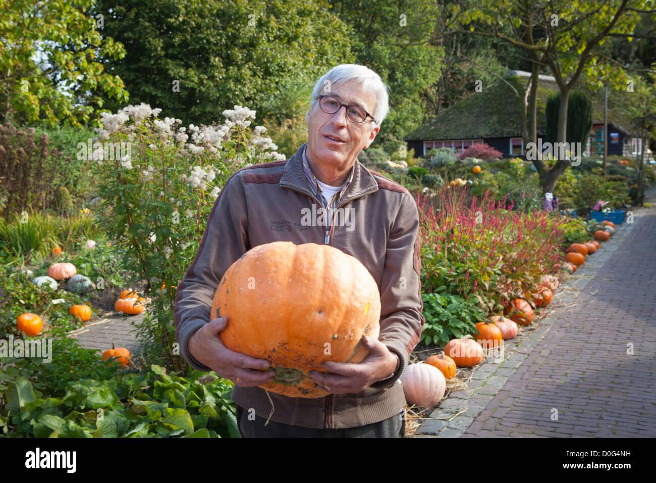 Portrait proud man with big pumpkin in a garden with pumpkins in the Klok and Peel museum in Asten in the Netherlands - Stock Image