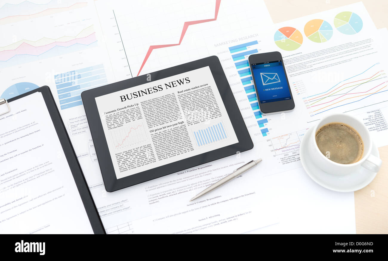 Modern business workflow with digital computer, mobile phone and some papers with charts and numbers on a desktop. - Stock Image