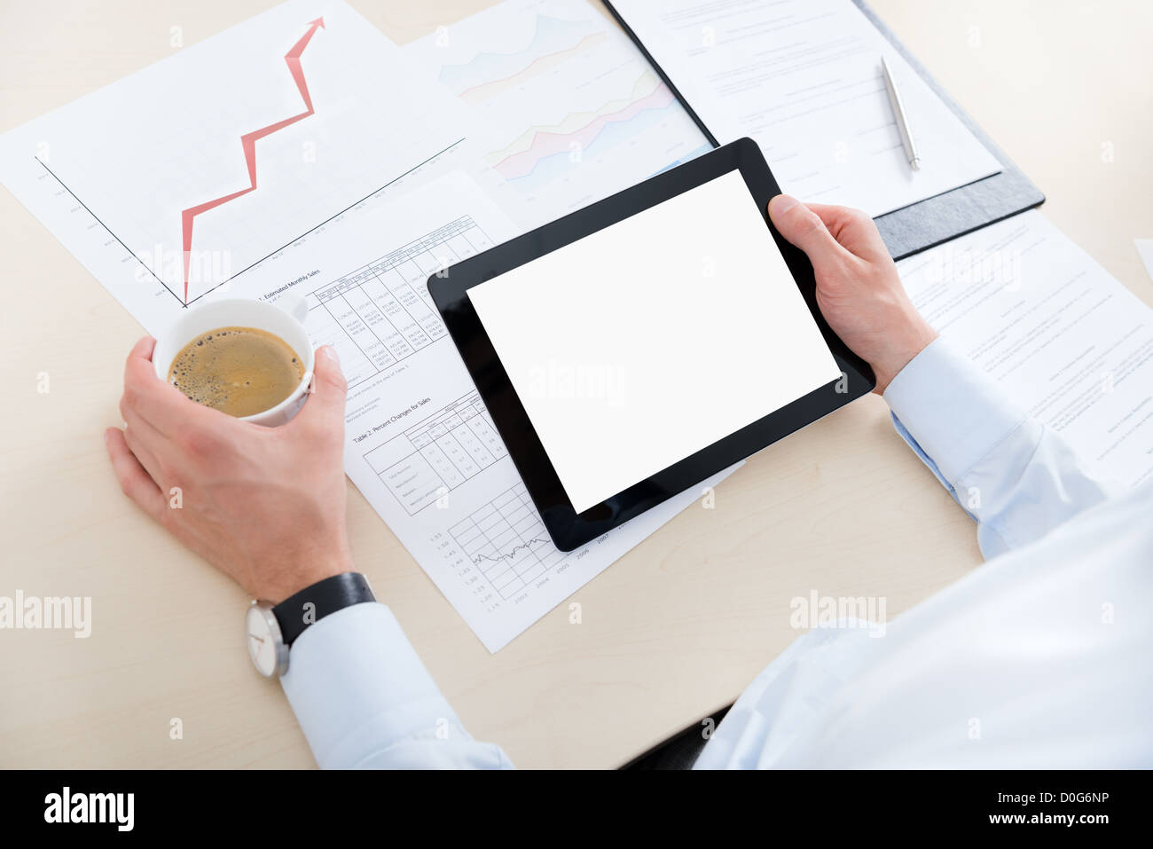 Businessman at workplace drinking coffee and looking at the blank digital computer. - Stock Image