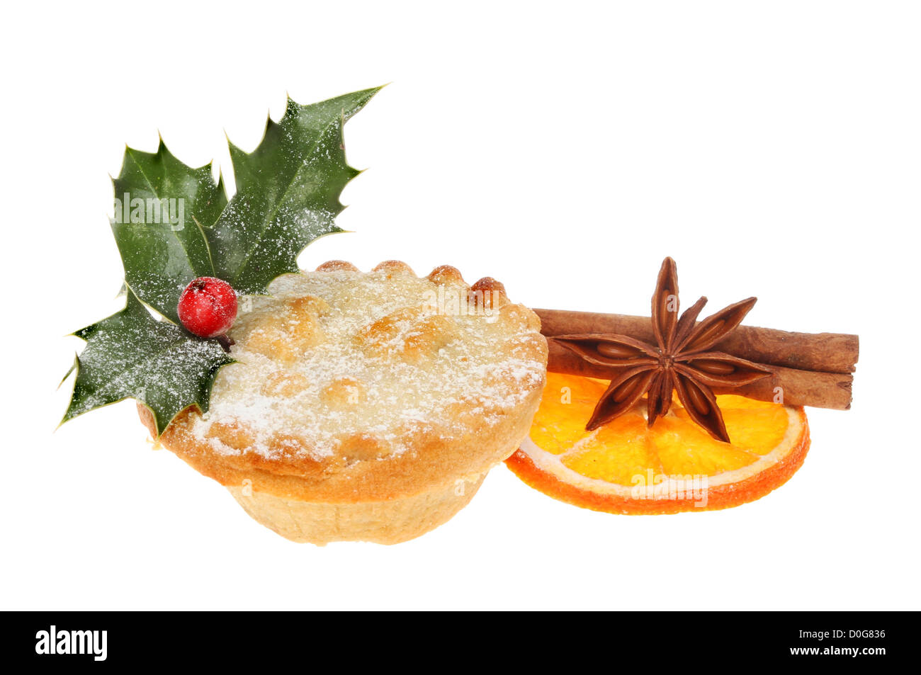 Mince pie decorated with holly and icing sugar with a slice of dried orange cinnamon and star anise - Stock Image