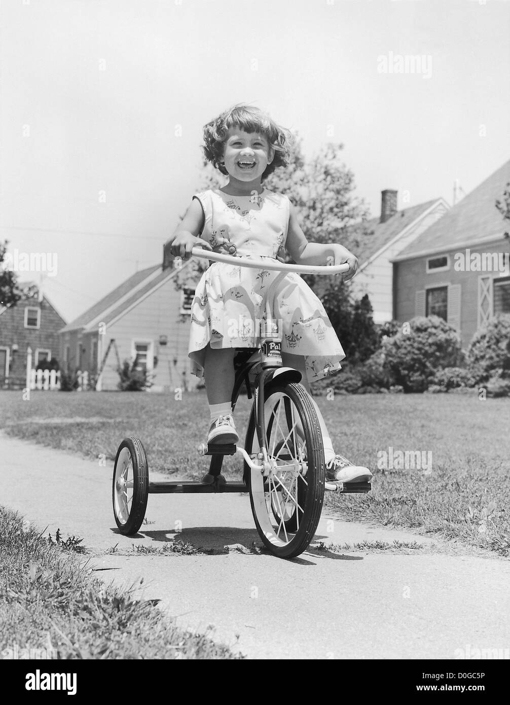 Smiling girl on tricycle - Stock Image