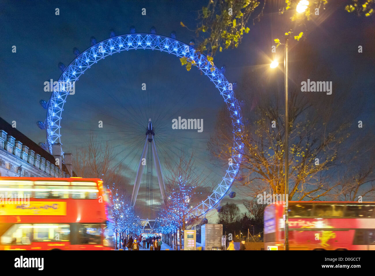 London Eye Millennium Wheel with blue Christmas Xmas lights and double-decker bus at dusk in winter, December - Stock Image