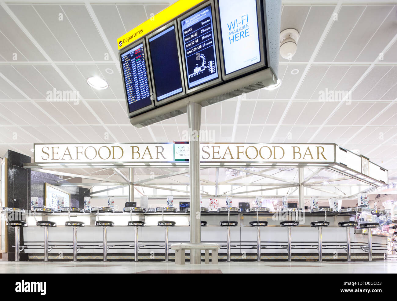 Gatwick Departure Lounge North Terminal Caviar House & Prunier Seafood Bar with departures display and Wifi - Stock Image
