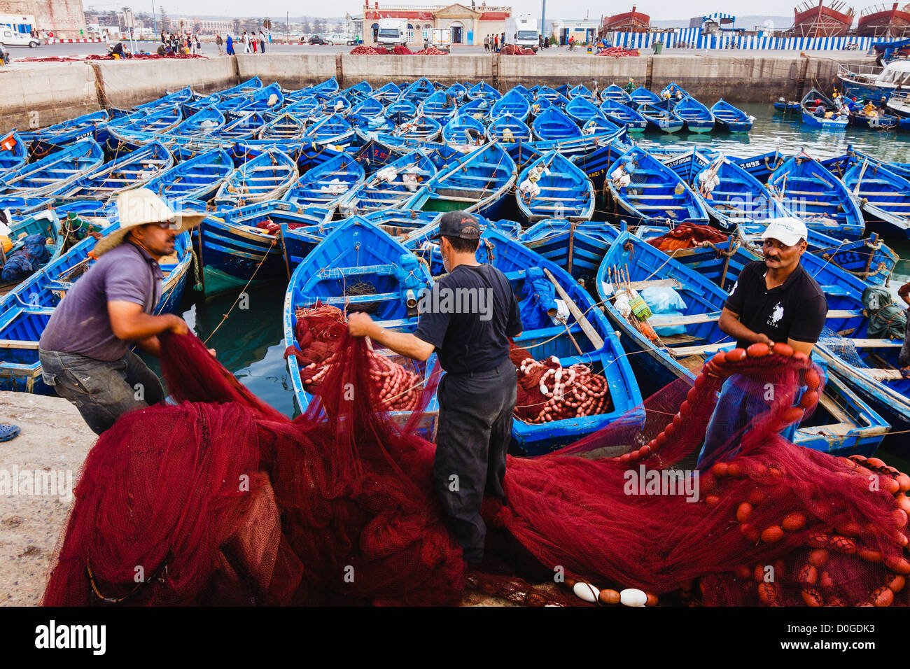 Fishermen collecting their fishing net at the harbor of Essaouira, Morocco - Stock Image