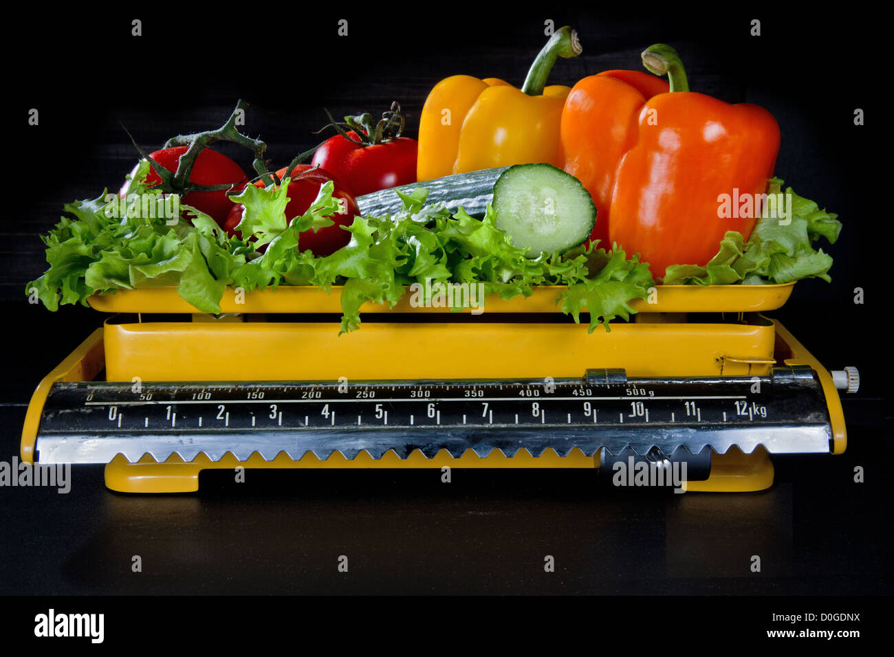 Fresh vegetables on an old yellow kitchen scale, with black background - weight loss concept - Stock Image
