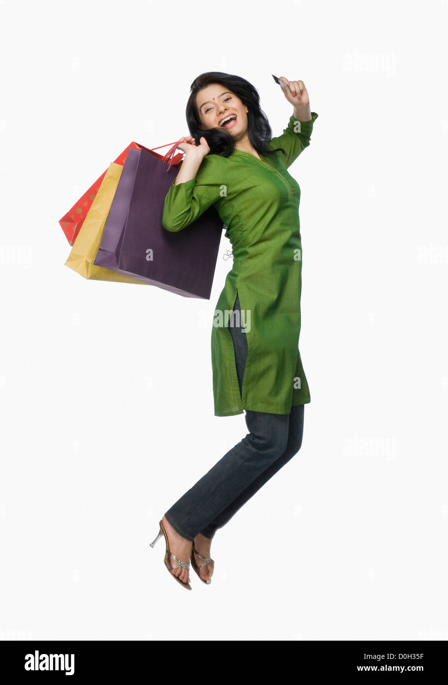 Young woman jumping with shopping bags and a credit card - Stock Image