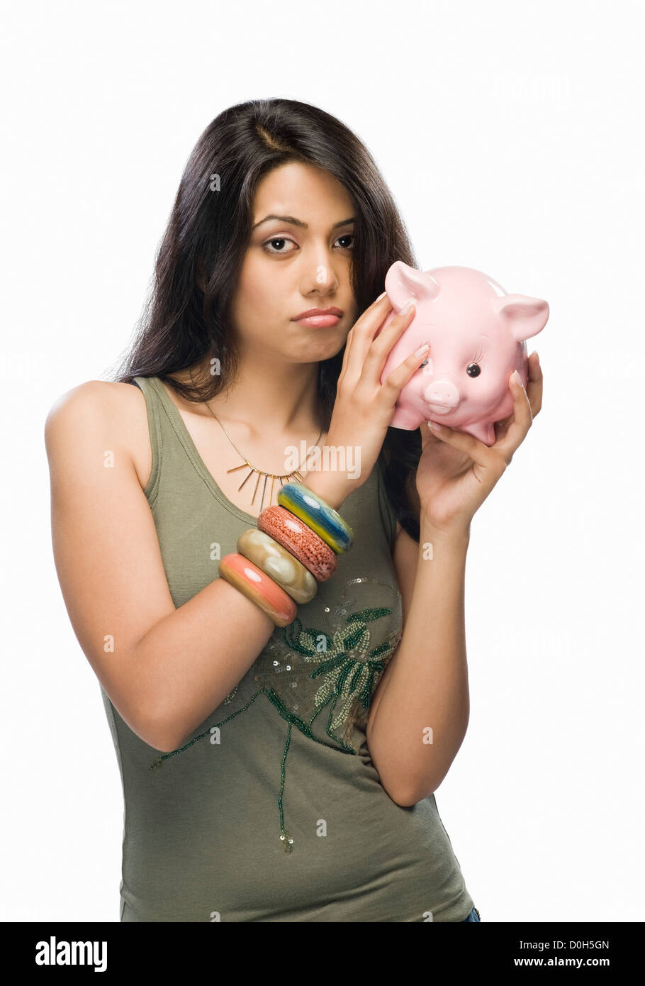 Portrait of a young woman worried with a piggy bank - Stock Image