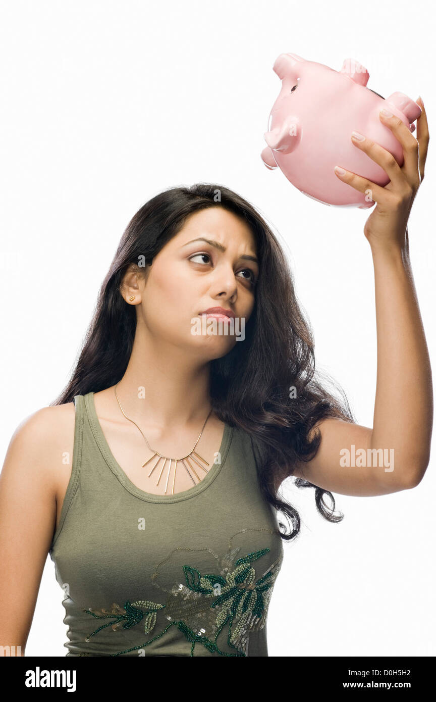 Young woman worried with a piggy bank - Stock Image