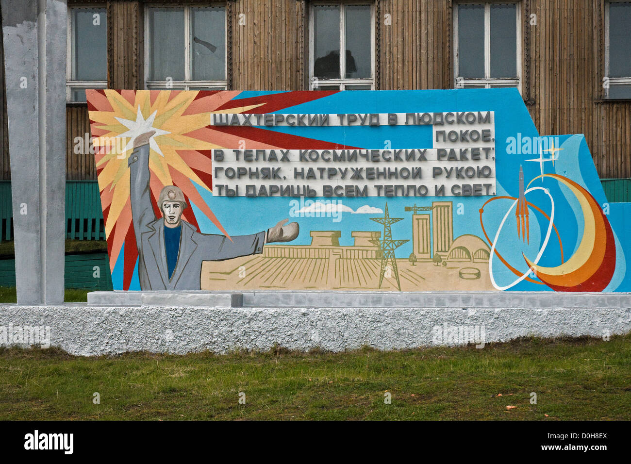 Sign depicting a coal miner and energy in Russian coal mining settlement of Barentsburg, Spitsbergen, in summertime. - Stock Image