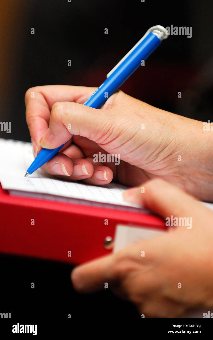 Delegate at a carers conference taking notes, London, UK. - Stock Image
