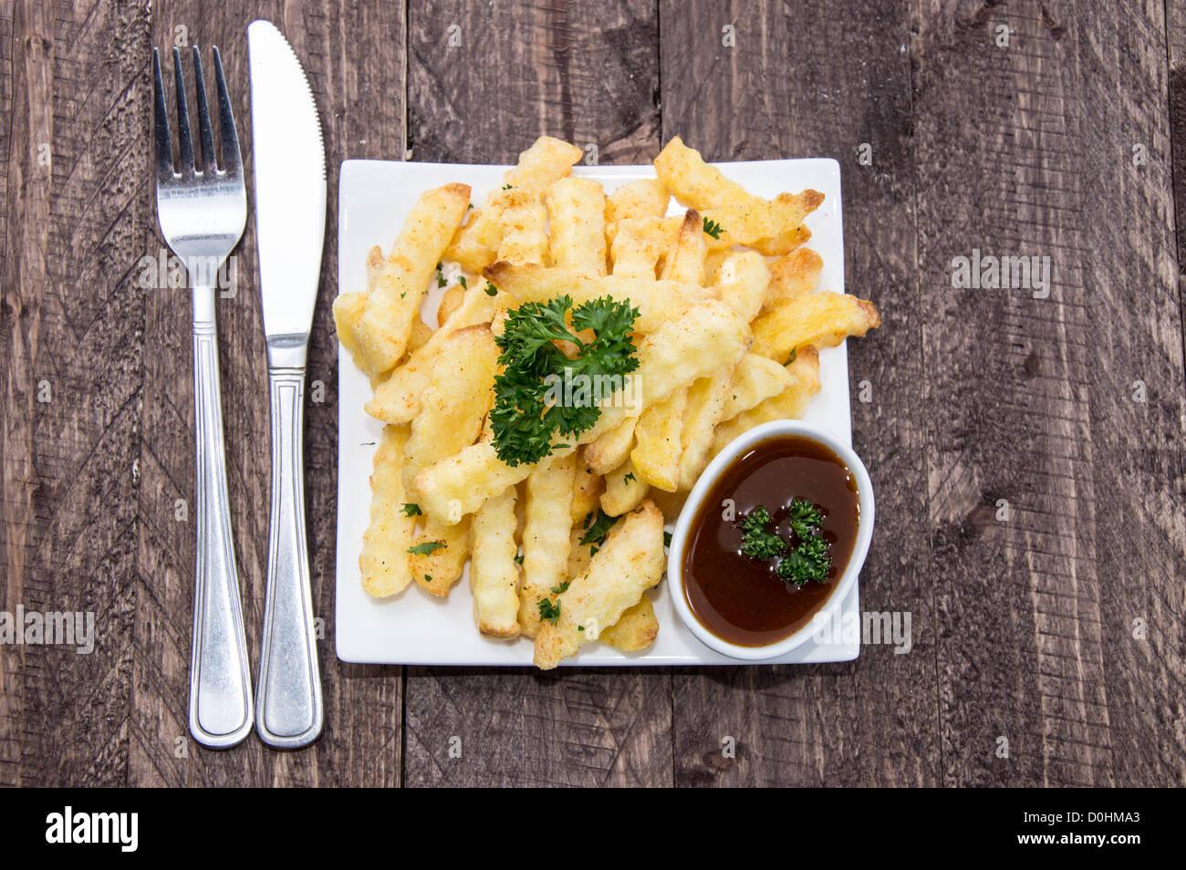 Fresh fried French Fries on wood - Stock Image