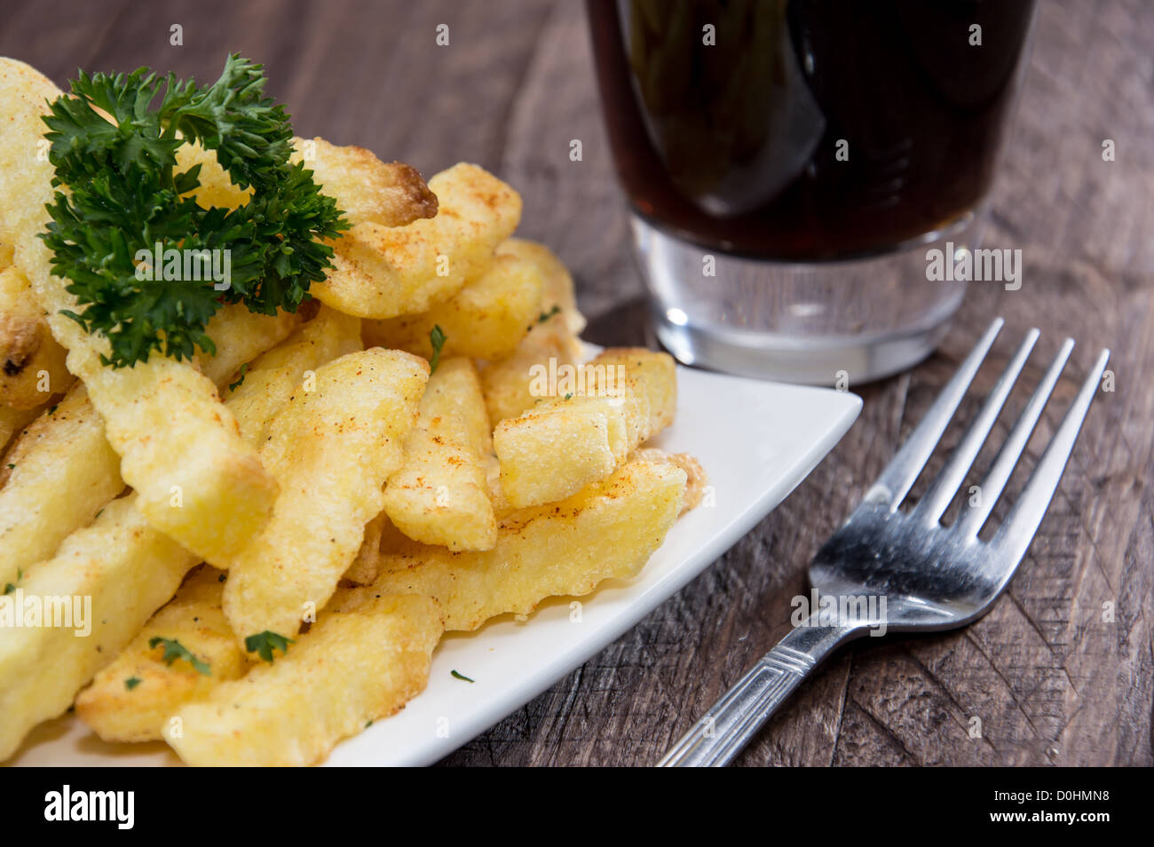 Plate with french fries on wooden background - Stock Image