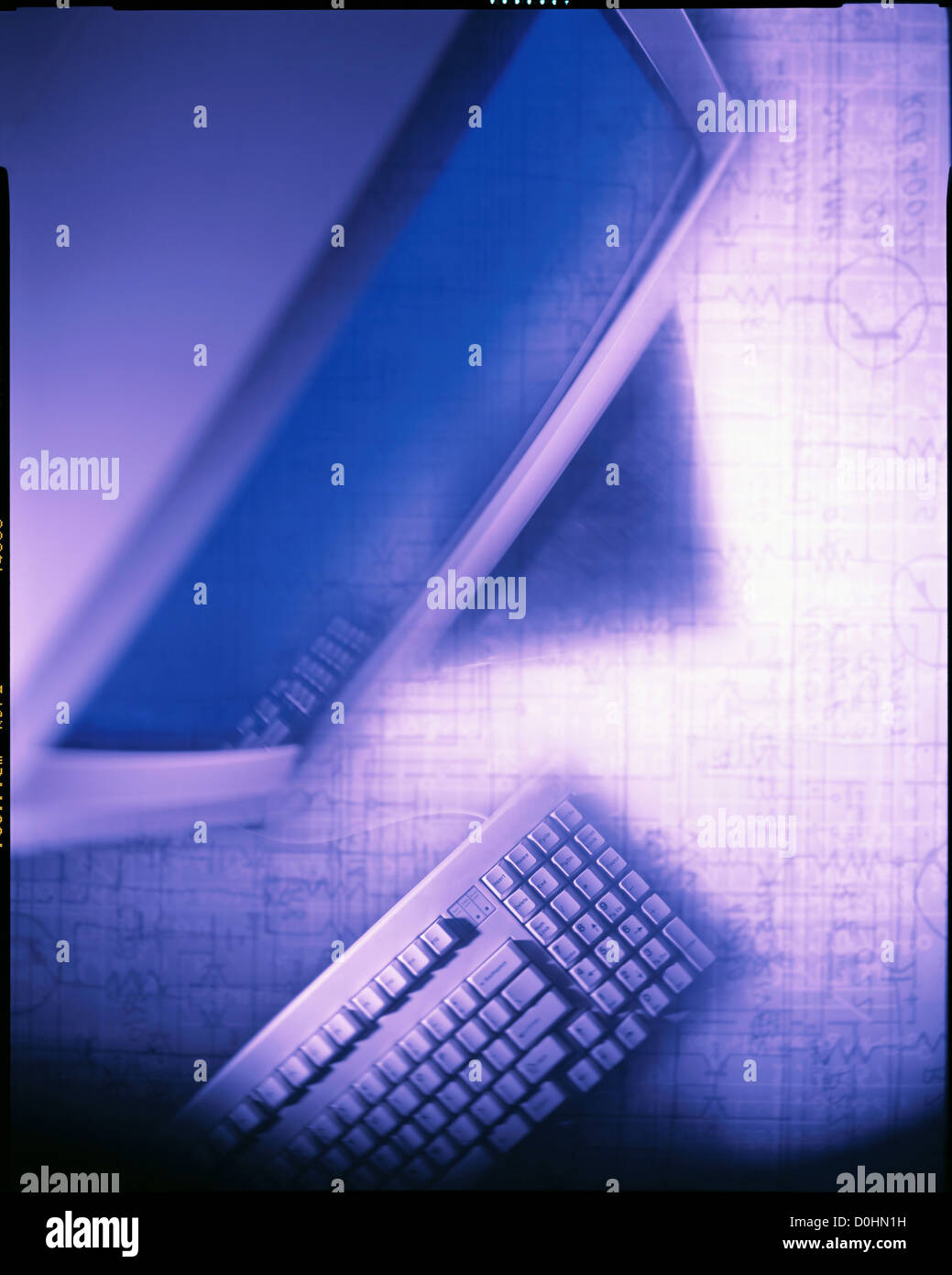 Computer Monitor and Keyboard With Schematics in the Background - Stock Image