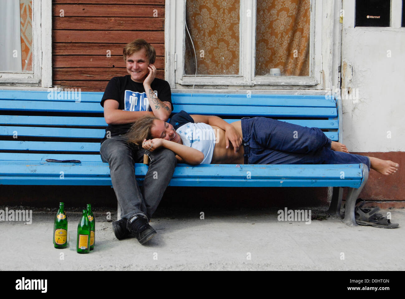 young couple mountaineer fun together beer bench romantic - Stock Image