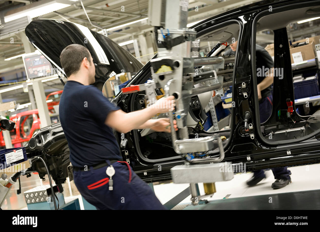 car factory worker on motor vehicle assembly line - Stock Image