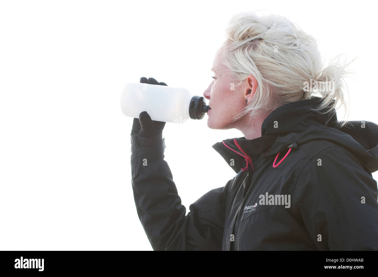 female jogger drinking from water bottle - Stock Image