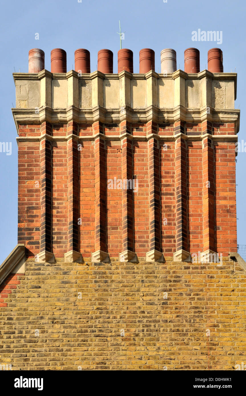 Cluster of nine brick built chimney flues & pots rising above gable end wall built in London stocks on old block - Stock Image