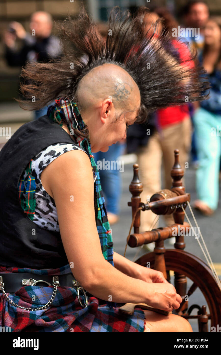 Woman with Mohican hairstyle spinning yarn, Edinburgh, Scotland - Stock Image