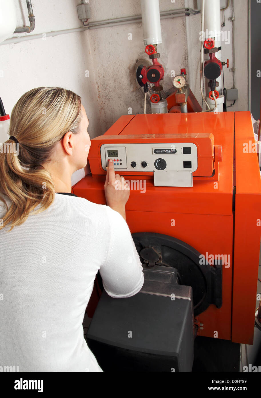 Woman adjusting the heating Stock Photo