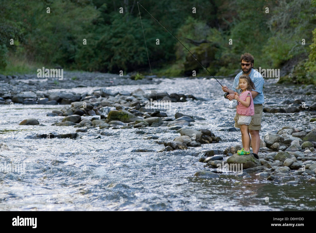 Father teaching daughter fly fishing on the North Fork of the Umatilla River, Oregon. - Stock Image