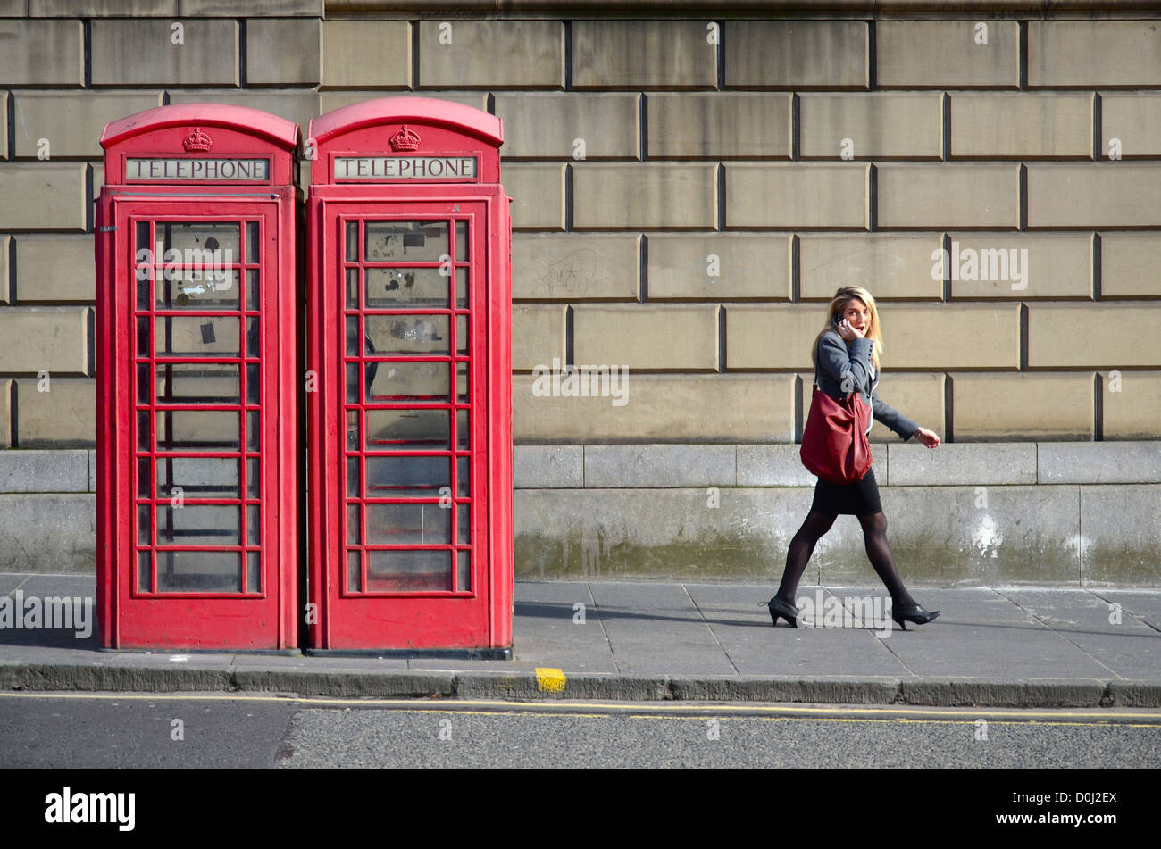 A young woman on a mobile phone strolls by a classic red telephone box on George IV Bridge in Edinburgh. - Stock Image