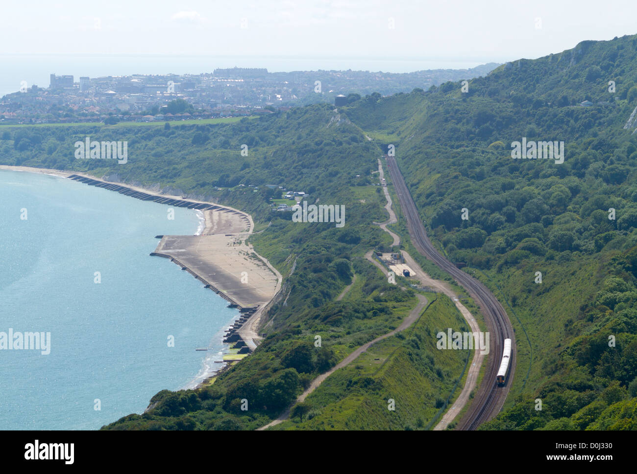 Train passing along the Kent coastline viewed from the cliffs above Folkestone Warren in Kent. - Stock Image