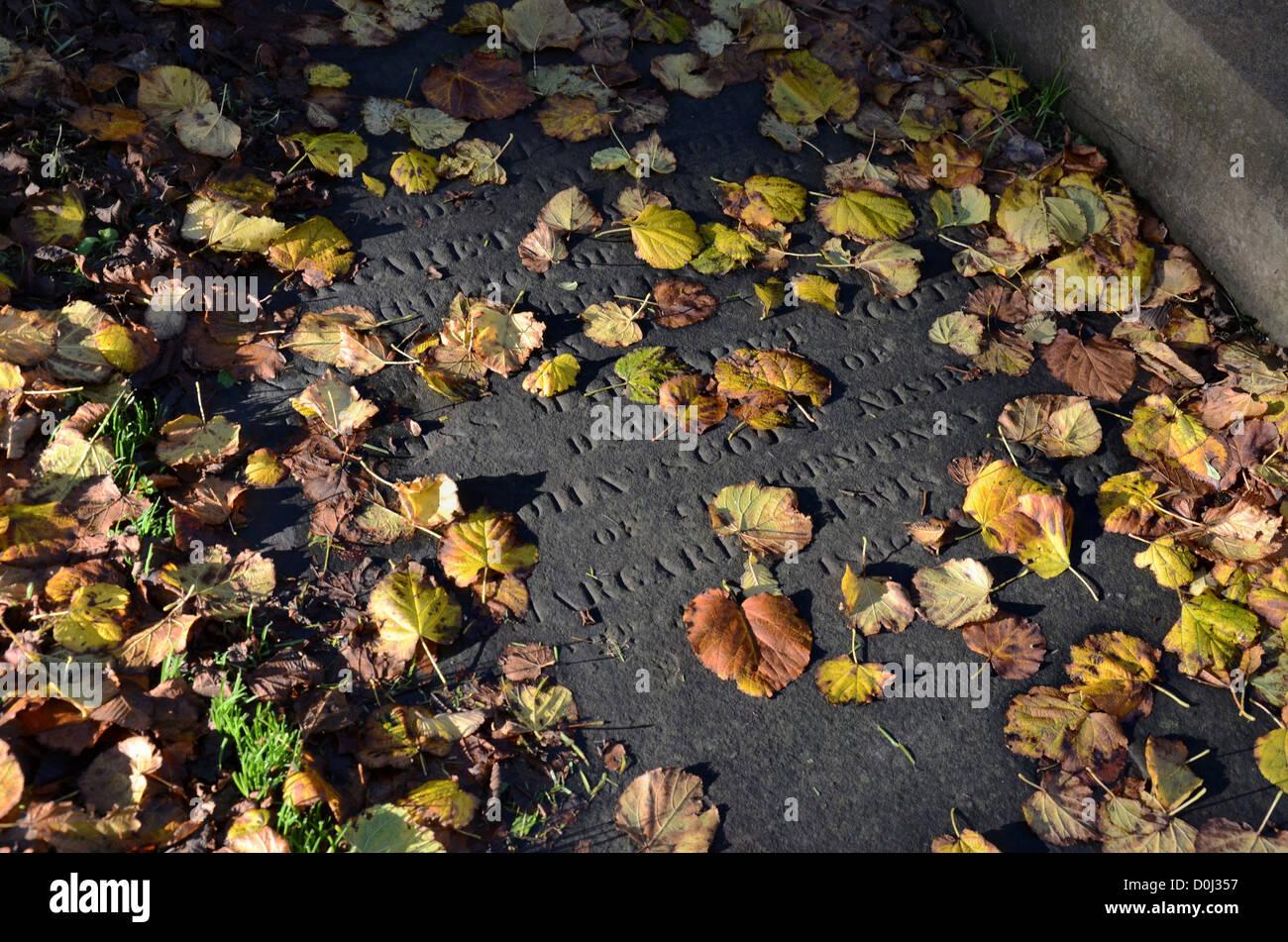 Autumn leaves on a gravestone in Greyfriars Kirkyard, Edinburgh, Scotland. - Stock Image