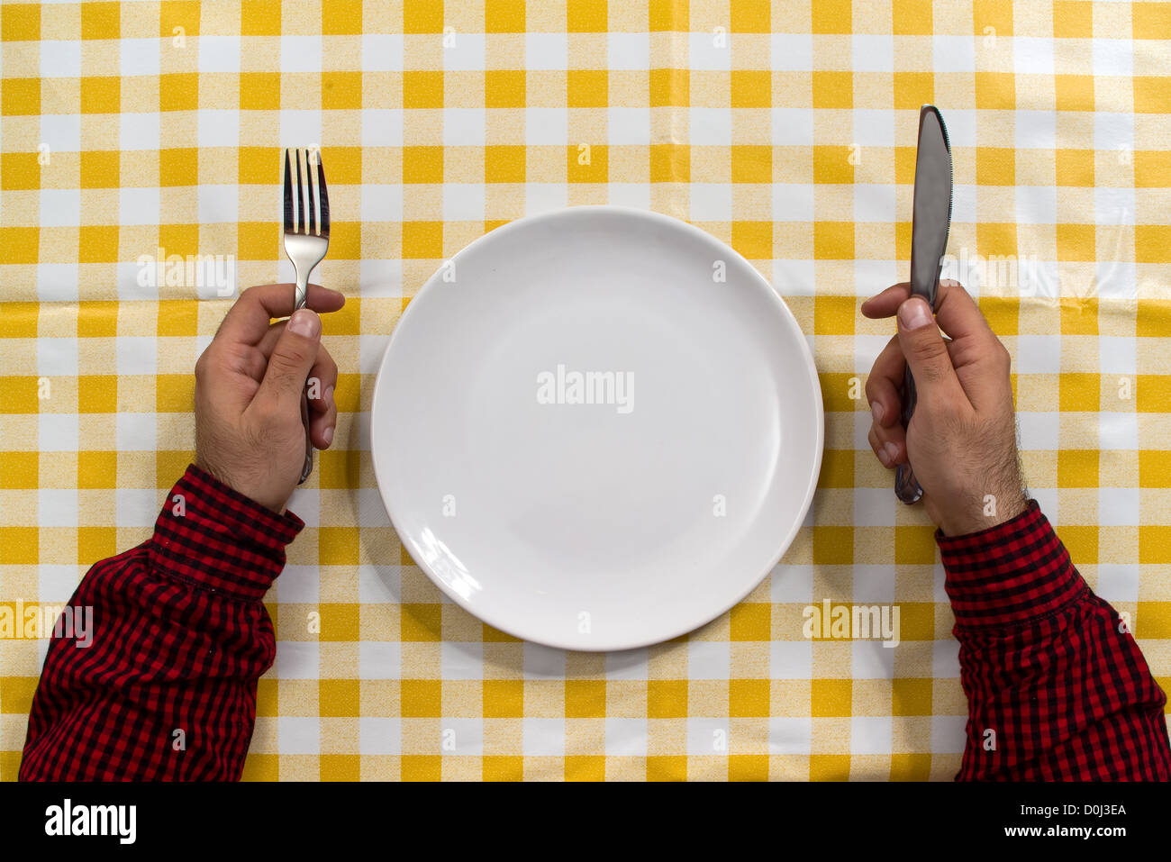 Man sitting at the dinner table with fork and knife and empty plate & Man sitting at the dinner table with fork and knife and empty plate ...