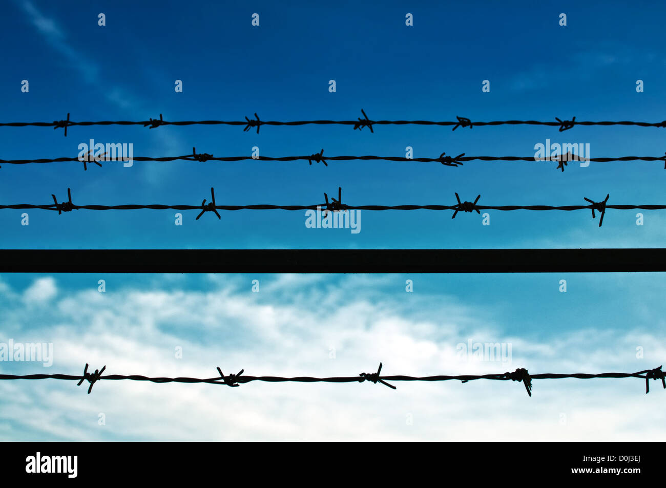 Barbed wire fence against the blue sky - Stock Image