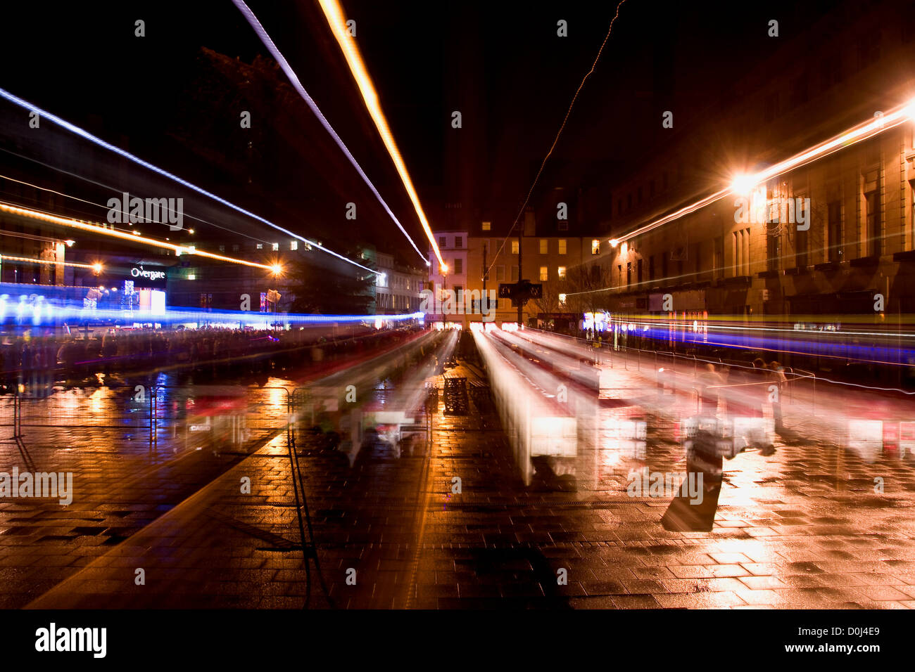 Crowds and street light reflections illuminating the city at night in the rain while using camera technique in Dundee,UK - Stock Image
