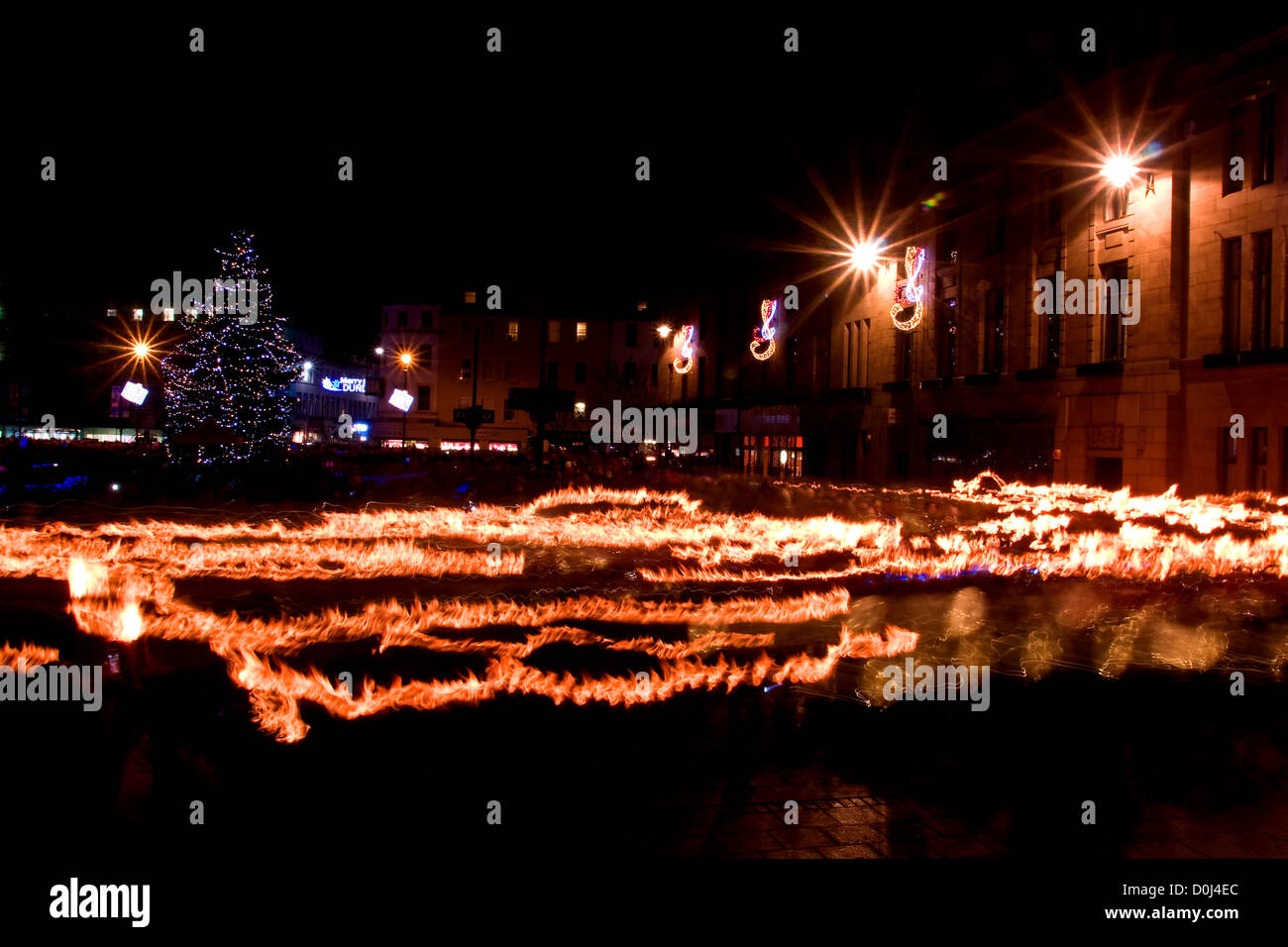 Crowds with lit torches parading around the city at night during the Christmas Tree Lights switch on in Dundee,UK Stock Photo